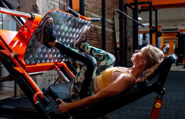 Frau in der sportbekleidung, die übung auf den beinen drückt maschine im fitnessstudio.