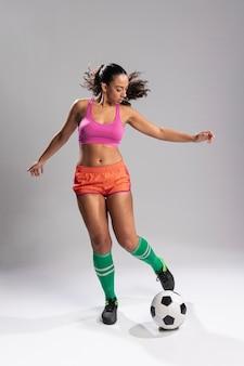 Frau in der sportkleidung, die fußball spielt