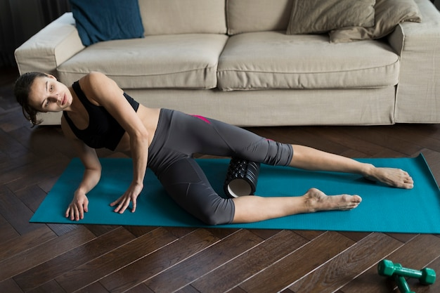 Frau in der sportkleidung, die übungen auf yogamatte tut