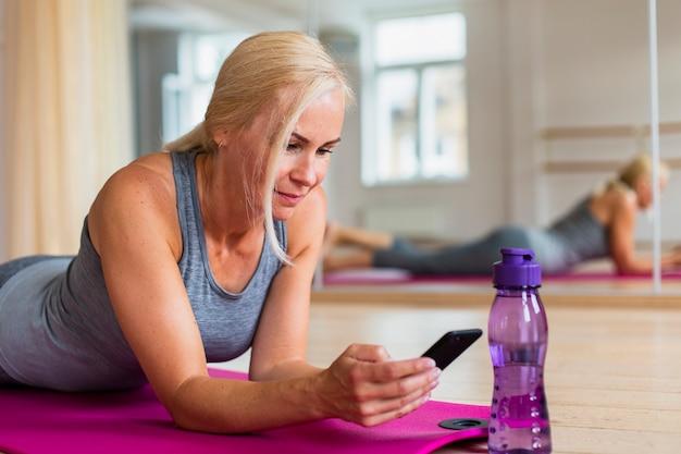 Frau in der sportkleidung ihr telefon überprüfend
