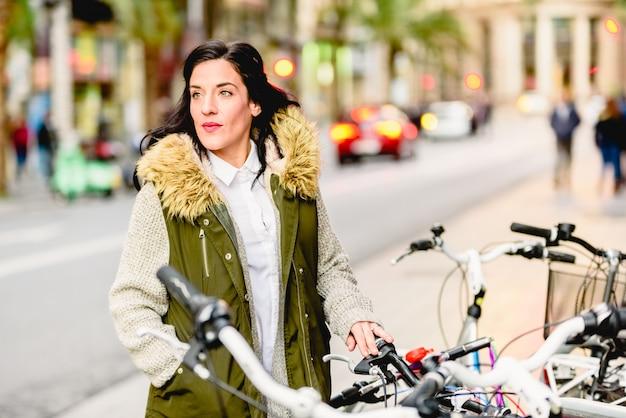 Frau in der stadt mit ihrem fahrrad, das ruhe aufwirft.