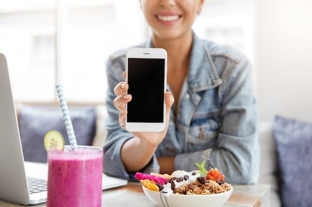 Frau in der stilvollen jeansjacke im kaffeehaus mit leerem smartphonebildschirm
