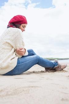 Frau in der stilvollen warmen kleidung, die am strand sitzt