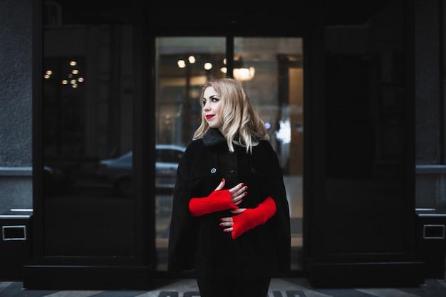 Frau in der straße mit roten handschuhen