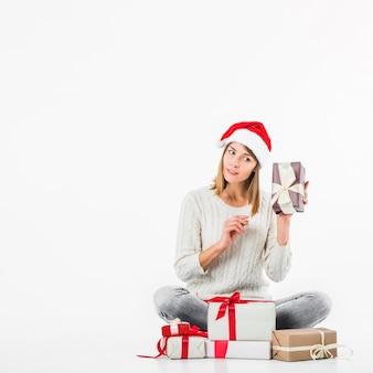 Frau in der strickjacke, die geschenkbox nahe ohr hält