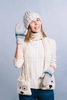 Frau in der strickjacke, die grußgeste zeigt