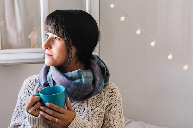Frau in der strickjacke mit cup