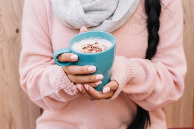 Frau in der strickjacke mit kaffeetasse