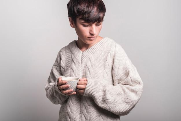 Frau in der strickjacke, welche die kaffeetasse steht gegen grauen hintergrund hält