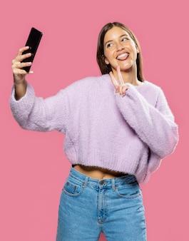 Frau in der studio-vorderansicht, die ein selbstfoto macht