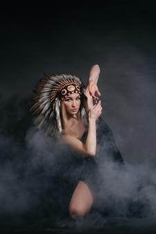 Frau in der tracht von indianern im rauche auf einem grauen hintergrund