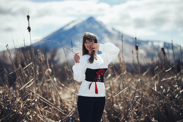 Frau in der traditionellen kleidung, die eine weide hält, verzweigt sich berg