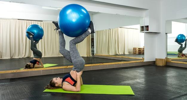 Frau in der turnhalle, die übungen mit großem ball macht