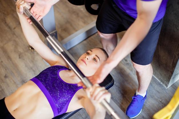 Frau in der turnhalle mit dem persönlichen eignungstrainer, der energiegymnastik mit einem barbell ausübt.
