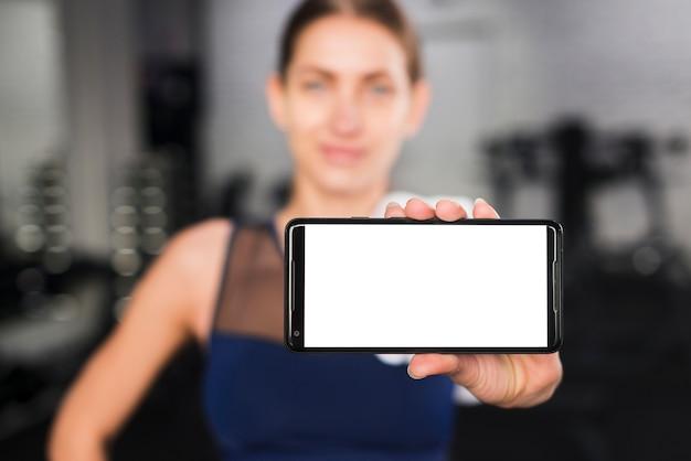 Frau in der turnhalle mit smartphoneschablone