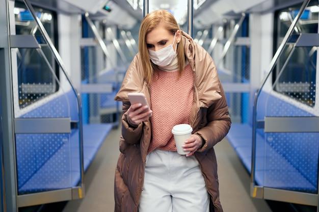 Frau in der u-bahnstation, die schützende chirurgische hygienemaske im gesicht trägt, verhindert das risiko des coronavirus