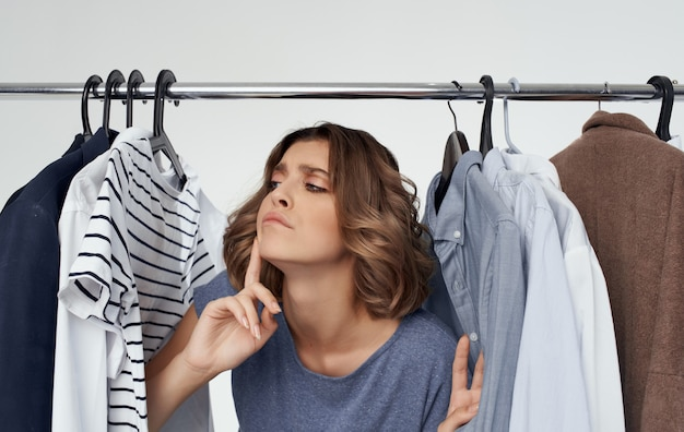 Frau in der umkleidekabine nahe modekleidung verwirrte blickart