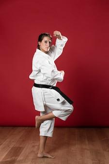 Frau in der uniform der kampfkünste karate ausübend