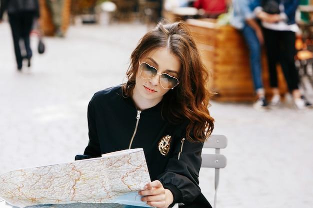 Frau in der ursprünglichen sonnenbrille sitzt am tisch im straßenkaffee mit touristischer karte