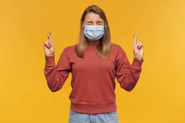 Frau in der virenschutzmaske im gesicht gegen coronavirus mit geschlossenen augen und gekreuzten fingern an beiden händen, die einen wunsch über gelber wand machen