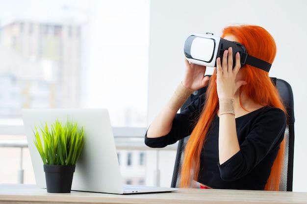 Frau in der virtuellen realität headset zeigt in der luft, während an ihrem arbeitsplatz im büro.
