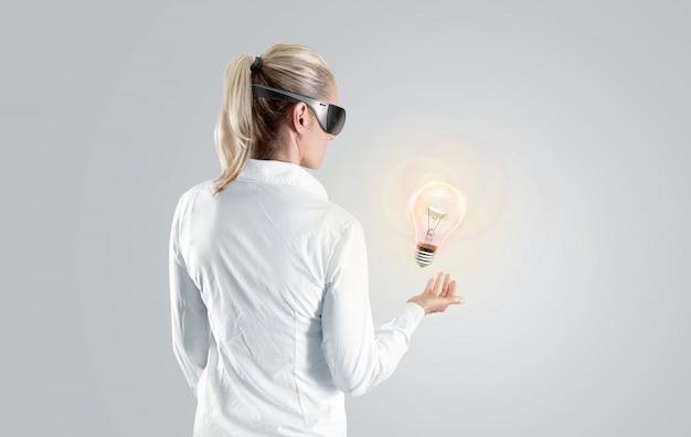 Frau in der virtuellen realitätsbrille, die auf das hologramm schaut, lokalisiert.