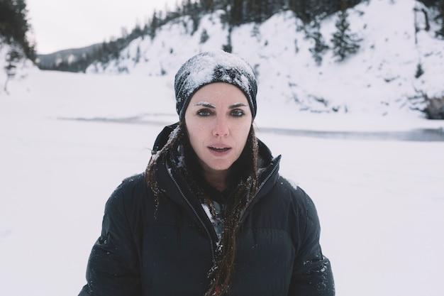 Frau in der warmen kleidung auf schneebedecktem hintergrund