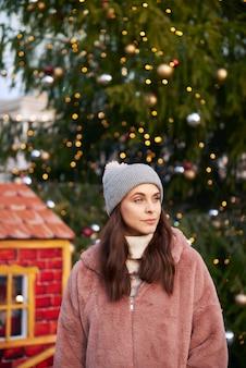 Frau in der warmen kleidung auf weihnachtsmarkt