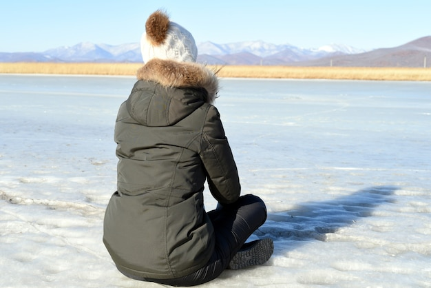 Frau in der warmen kleidung, die auf dem eis sitzt und schneebedeckte berge betrachtet