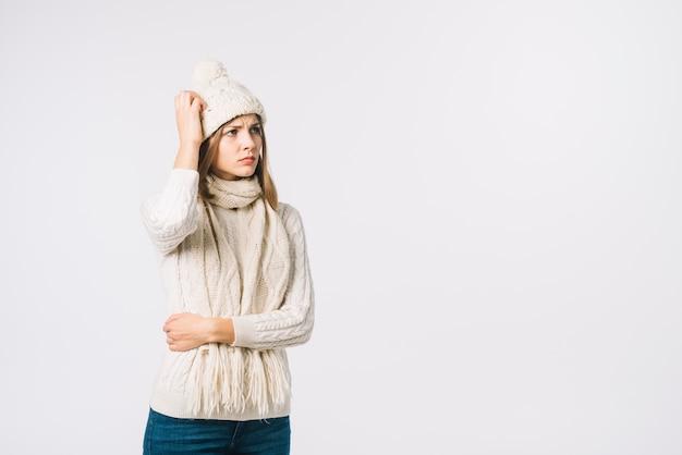 Frau in der warmen kleidung, die kopf verkratzt
