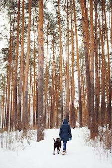 Frau in der warmen kleidung, die mit hund im winterwald spielt. aktiver winterlebensstil.