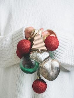 Frau in der warmen weißen strickjacke, die weinlese-weihnachtsbaumspielzeug in den händen hält
