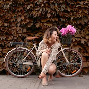 Frau in der weiblichen kleidung wirft auf fahrrad an einem sommertag auf