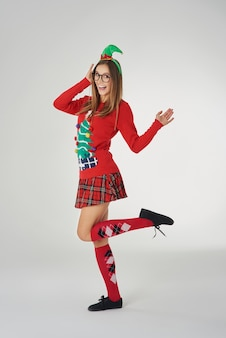 Frau in der weihnachtskleidung an der grauen wand