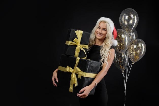 Frau in der weihnachtsmannmütze mit geschenkboxen an der schwarzen wand. goldene luftballons und weihnachtsferien.