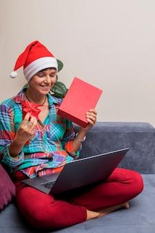 Frau in der weihnachtsmannmütze mit geschenken und laptop online