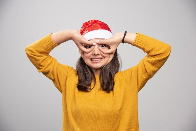 Frau in der weihnachtsmütze, die ihre pupillen zeigt.