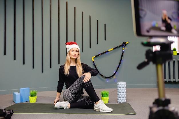 Frau in der weihnachtsmütze fitness-trainer aufzeichnung video-blog mit kamera auf stativ.