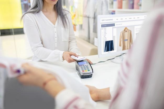 Frau in der weißen bluse, die zahlung für bestellung mit smartphone und verkäufer hinter chemischer reinigungstheke macht