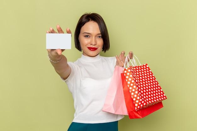 Frau in der weißen bluse und im grünen rock, die einkaufspakete halten und weiße karte zeigen