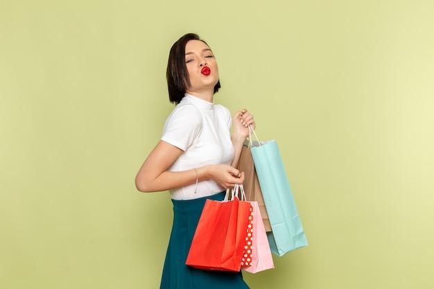 Frau in der weißen bluse und im grünen rock, die einkaufspakete halten