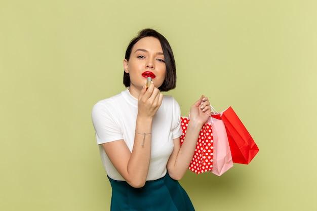 Frau in der weißen bluse und im grünen rock, die einkaufspakete und lippenstift halten