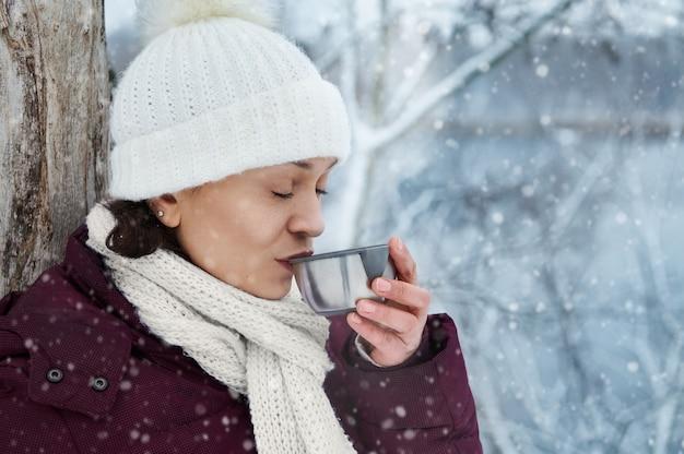 Frau in der weißen gestrickten wollmütze, die schönen verschneiten tag beim trinken des heißen tees genießt. fallender schnee