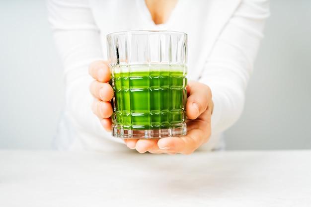Frau in der weißen kleidung, die das glas mit japanischem matcha-tee oder grünem smoothie hält