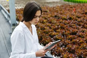 Frau in der weißen Laborkleidung überprüft Salat und Kohl in einem Gewächshaus unter Verwendung einer Tablette