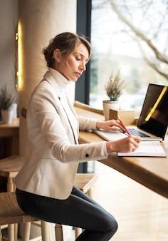Frau in der weißen reihe, die an laptop am business-lunch arbeitet