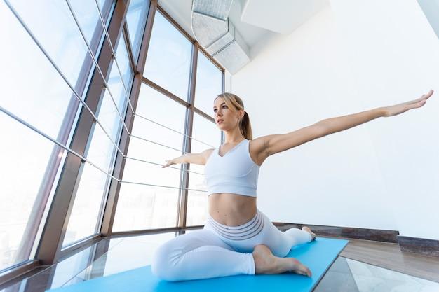 Frau in der weißen sportbekleidung, die yoga tut