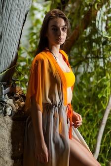 Frau in der weißen tunika im tropischen garten mit palme
