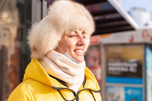 Frau in der winterkleidung an einem kalten tag, der an einer bushaltestelle auf einen bus wartet