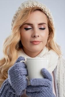 Frau in der winterkleidung köstlichen kaffee trinkend, um warm zu werden